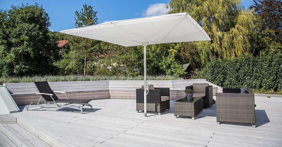 Holzterrasse mit Gartenmöbeln und Sonnenschirm