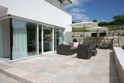 Steinterrasse mit Terrassenmöbeln und Sonnenschirm